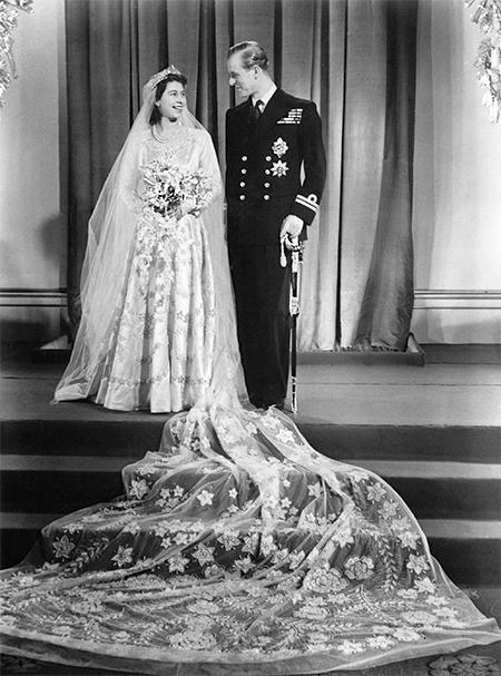 Свадьба Елизаветы и Филипа состоялась 20ноября 1947 года в Вестминстерском аббатстве. На пошив наряда невесты правительство выделило 200 талонов на одежду (со времен войны королевство жило по карточной системе, которая была отменена только в 1954 году). Британский дизайнер Норман Хартнелл создал платье из сатина цвета слоновой кости, вдохновившись картиной «Весна» Боттичелли. Расшил его серебряной нитью, кристаллами и жемчугом. Наряд дополнял четырехметровый шлейф из тюля