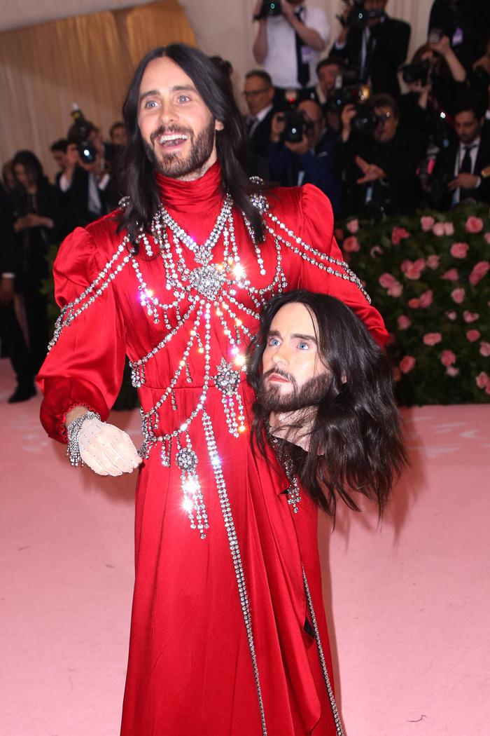 Джаред Лето в наряде от Gucci, который состоял из алого платья обильно декорированного стразами, и со второй головой на Met Gala в 2019 году.